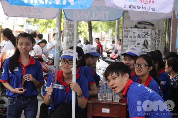 Đội sinh viên tình nguyện trực chiến tại cổng trường, phát nước cho thí sinh cũng như phụ huynh đưa con đi thi.