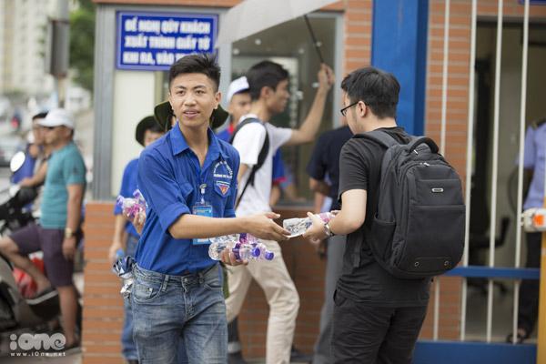 Dù trời mưa, đội sinh viên tình nguyện vẫn nhiệt tình phát nước cho các thí sinh.