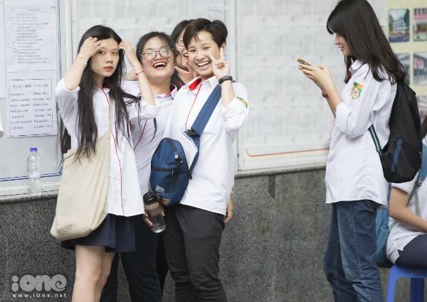 Học sinh túm tụm chia sẻ niềm vui với nhau.