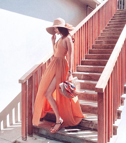 Chiếc váy màu cam xẻ tà bay bổng giúp Lan Khuê trông như một nàng thơ giữa khung cảnh lãng mạn.