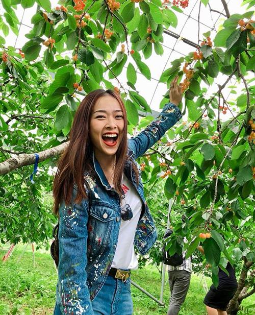 Diệp Bảo Ngọc không ngại khoe nụ cười thả ga khi được vào vườn tự do hái quả.