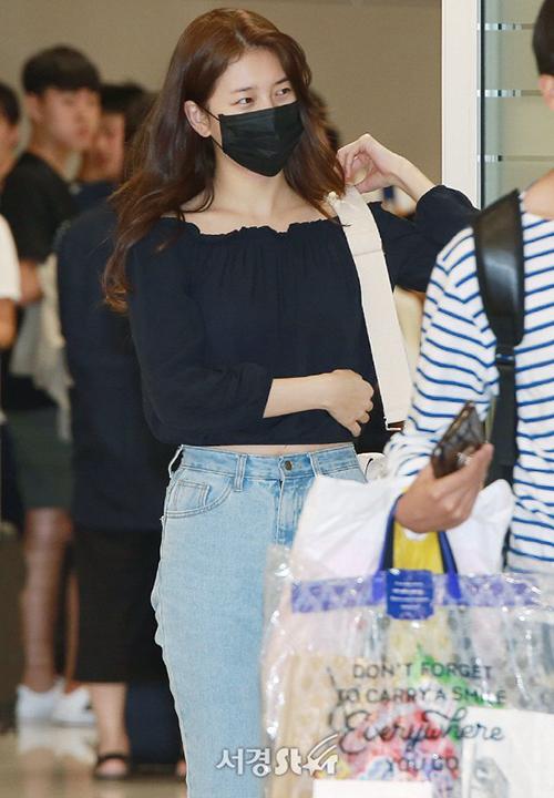 Suzy dùng khẩu trang che vẻ mệt mỏi khi về Hàn. Kiểu áo trễ vai giúp nữ ca sĩ khoe xương quai xanh gợi cảm.