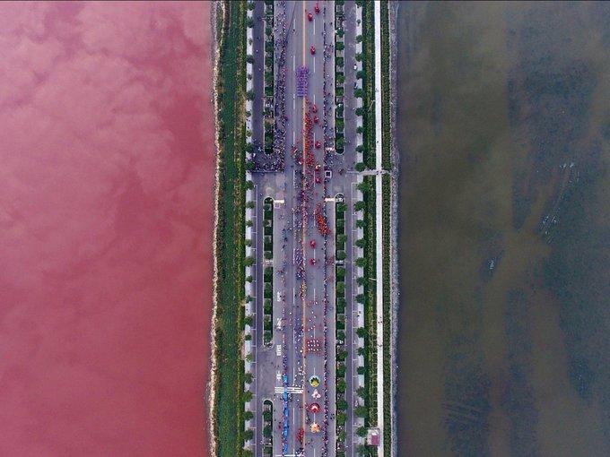 """<p> Con đường chia đôi hồ muối thành """"hai nửa"""" riêng biệt, trong đó mặt hồ phía bên trái có màu đỏ của tảo.</p>"""