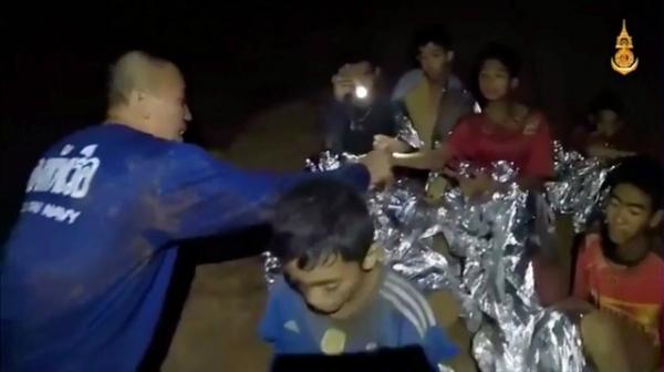 Thành viên cứu hộ ở lại cùng các cậu bé. Ảnh: Reuters.