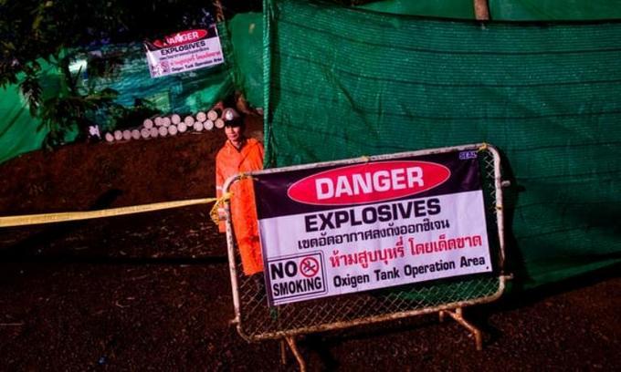 <p> Một cảnh sát Thái Lan đứng gác ở lối vào của hang động từ sáng sớm. Khu vực này được phong tỏa và đặt biển báo nguy hiểm. Ảnh: AFP</p>