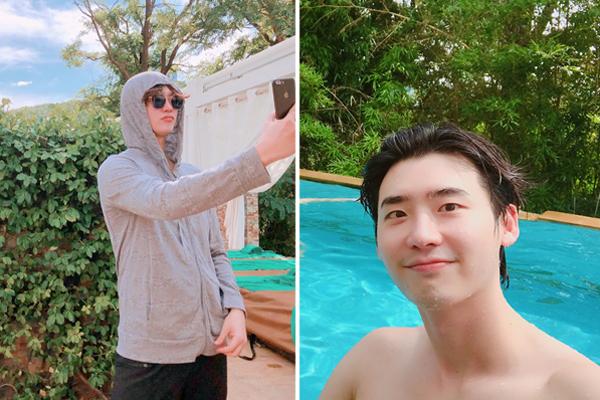 Lee Jong Suk mặc áo, đội mũ kín mít chụp ảnh dưới nắng trước khi cởi đồ xuống nước bơi lội.