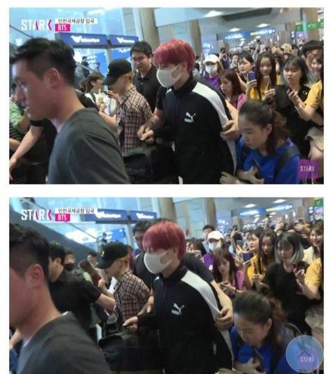 Jung Kook bị một cô gái ôm chặt khi di chuyển ở sân bay.