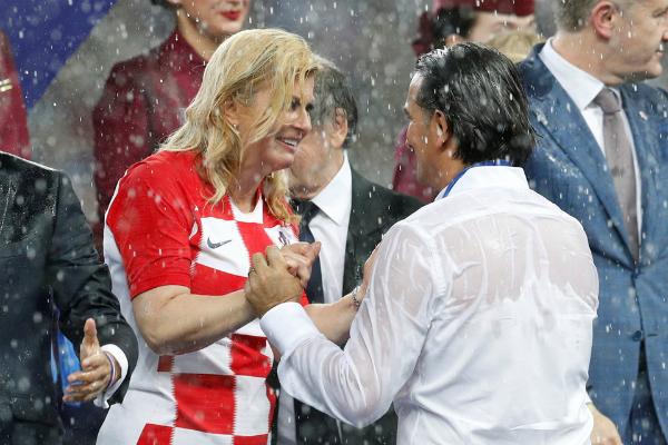 Kolinda Grabar-Kitarovic không ngại dầm mình dưới cơn mưa động viênhuấn luyện viên, tuyển thủ đội nhà. Ảnh: Reuters
