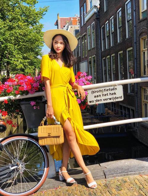 Để có những bức ảnh street style đẹp mắt, Hương Giang chọn chủ yếu những bộ váy áo màu sắc cho chuyến đi lần này. Với từng thành phố đi qua, người đẹp cũng rất khéo diện đồ phù hợp khung cảnh. Khi đến Amsterdam ngập tràn hoa, Hoa hậu hóa quý cô cổ điển trong chiếc váy vàng bèo, kết hợp túi xách Chanel.