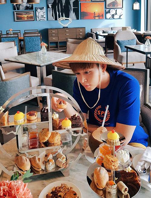 Jun Phạm đội mũ cối ngồi thưởng thức trà bánh sang chảnh trong một khu resort.