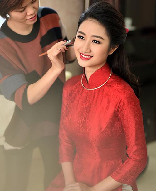 Để phù hợp với chiếc áo dài đang mặc, Hoa hậu Thu Ngân được chuyên gia trang điểm tô môi son rực rỡ.