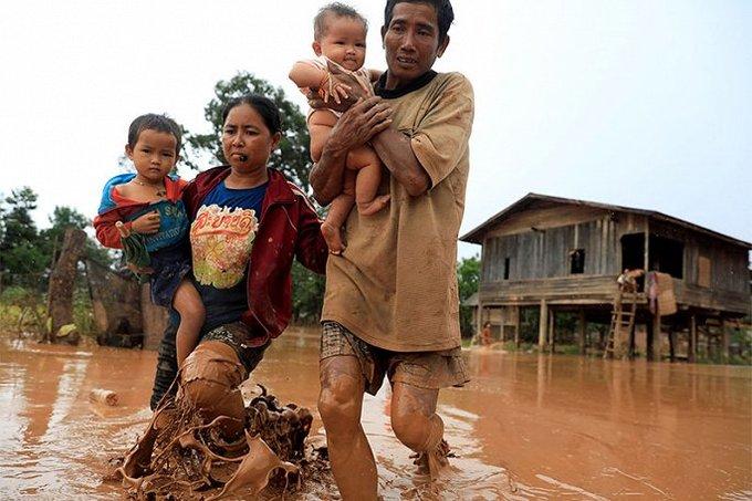 <p> Cha mẹ tay bồng tay bế con thơ lội bùn để trở về nhà.</p>