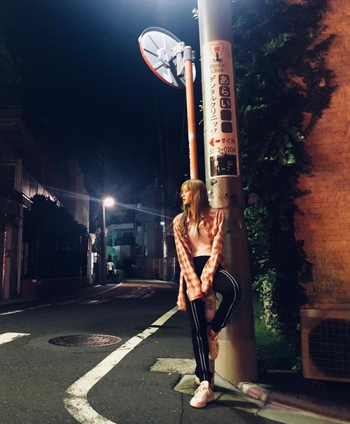 Lisa (Black Pink) gác chân lên cột để tạo dáng street style cho chất.