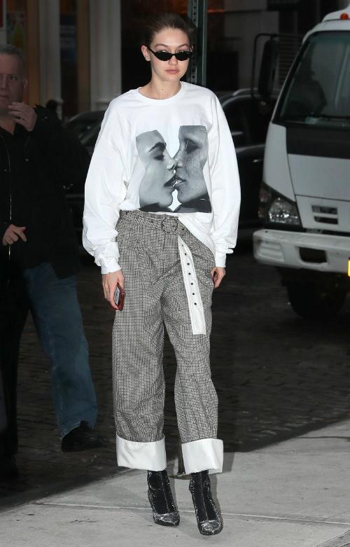Gigi Hadid luôn biết cách mix item casual để tạo thành những bộ cánh chất chơi: áo hoodie oversize phối cùng quần ống rộng xắn gấu họa tiết kẻ sọc bản nhỏ củaYigal Azrouel.