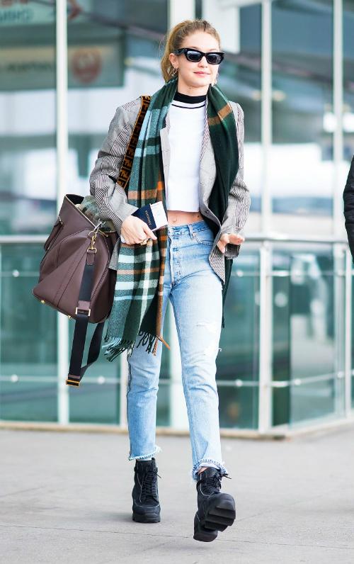 Thời trang sân bay cool hết nấc của cô nàng: blazer Maison Margiela, quần jeans Re/Done, kính mátBec + Bridge x Pared và tạo điểm nhấn bằng chiếc khăn quàng gam xanh rêu ấm áp.