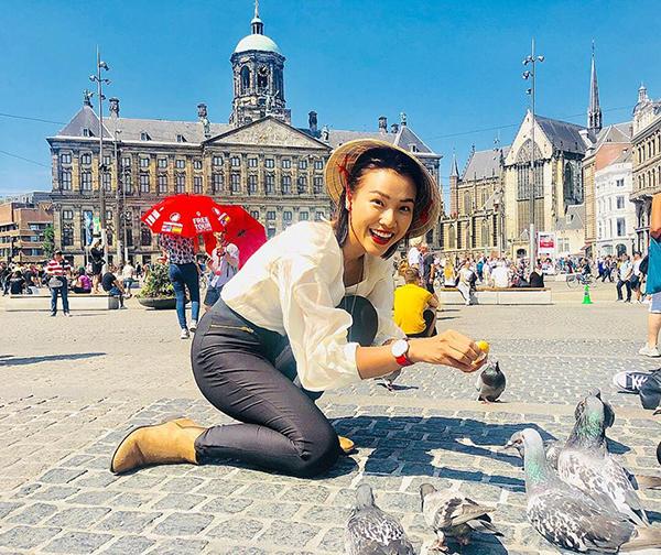 Hoàng Oanh đội nón lá tí hon cho chim bồ câu ăn trên quảng trường Dam ở Hà Lan.