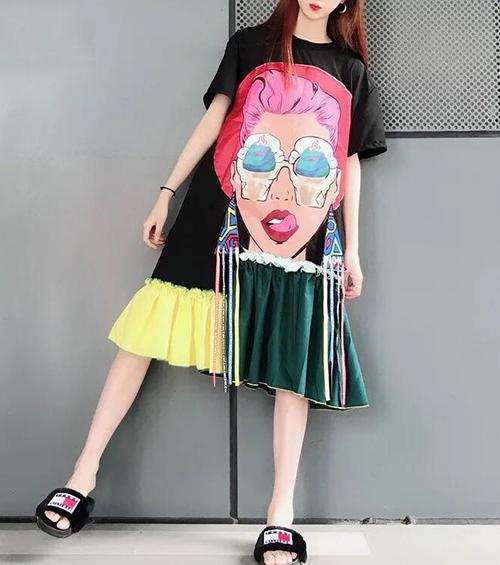 Đặc trưng của chiếc váy này là thân in họa tiết cô gái đeo kính rất cá tính. Phần gấu váy đắp vải vạt lệch màu sắc đối lập lạ mắt. Trang phục càng thêm nổi bật với chi tiết dây tua rua.