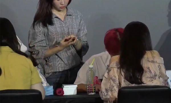 Nữ nhân viên thản nhiên kiểm tra điện thoại của fan trong buổi ký tặng.