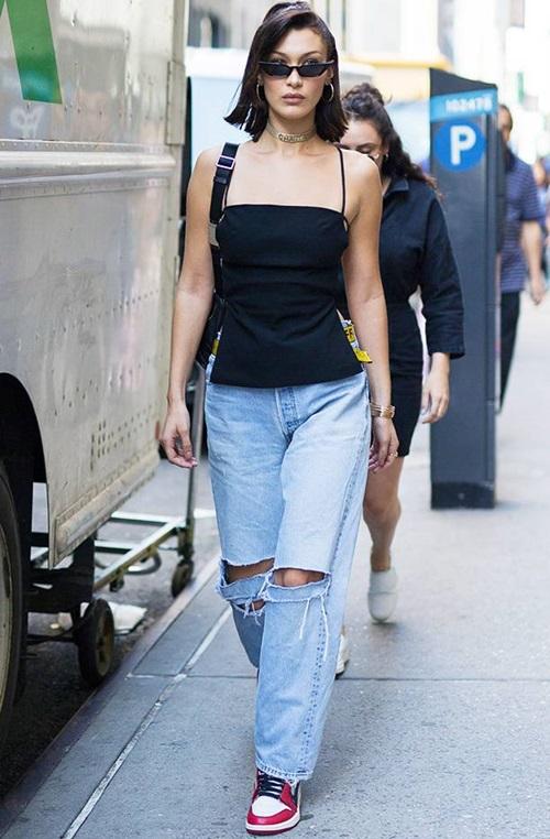 Cũng giống với nhiều IT girls, streetstyle của Bella Hadid chuộng những item thoải mái, khỏe khoắn mang phong cách của thập niên 90-2000: quần jean rộng thùng thình, áo hai dây, choker, kính mát tí hon và giày thể thao cổ điển.