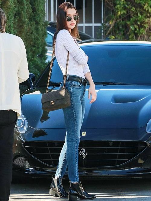 Set đồ đơn giản nhưng vẫn cuốn hút của Bella: áo thun trắng, quần jean Agolde, boot Chelsea Asos, túi xách Chanel và kính râm Ray Ban dáng tròn.