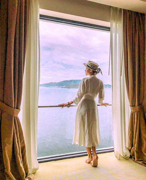 Minh Hằng trông như cô tiểu thư quý tộc đứng ngắm biển từ phòng khách sạn hạng sang.