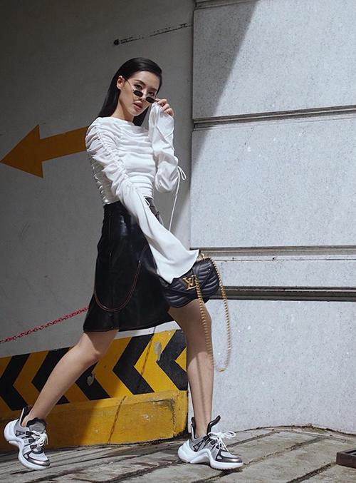 Khánh Linh tiếp tục chứng tỏ là fashionista thượng thừa khi diện bộ váy đen trắng nữ tính với túi xách và sneakers rất mạnh mẽ của Louis Vuitton.