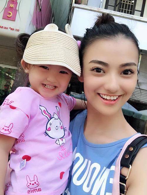 Hồng Quế cười tươi rói bế con gái đi chơi.