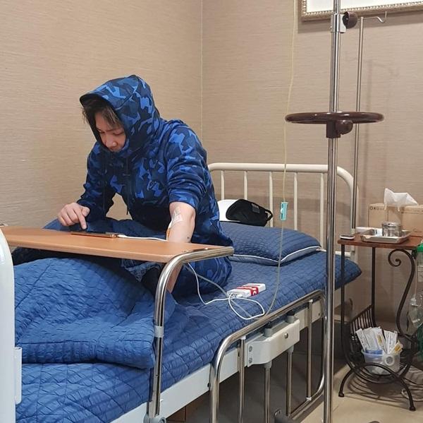 Lee Hong Ki phải truyền nước trong bệnh viện nhưng cũng không chịu nằm yên mà mải mê ngồi chơi game trên di động.