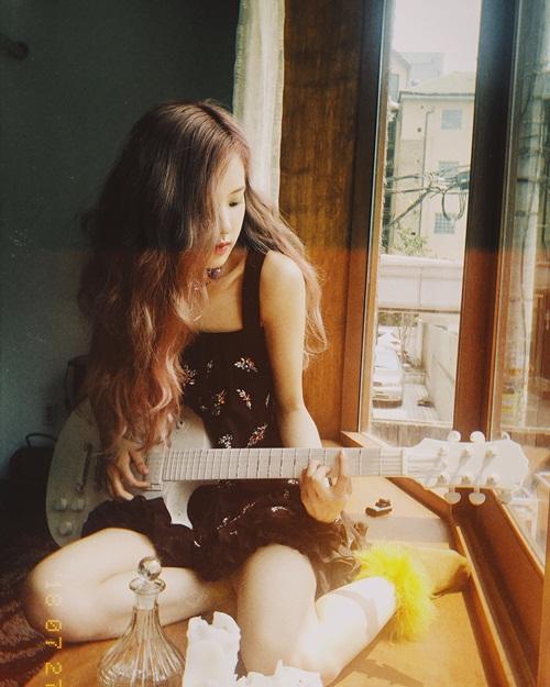 Rosé ôm đàn guitar bên cửa sổ tạo nên khung cảnh đẹp mộng ảo.