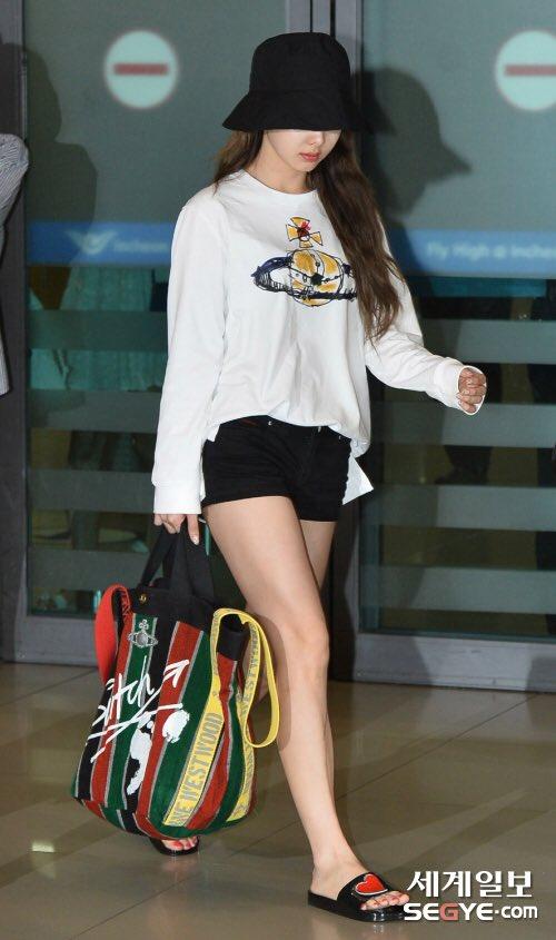 Na Yeon cầm theo túi xách to như đi chợ, mũ vé số và dép lê. Fan cho rằng ra sân bay thì cần sự thoải mái hơn là những item cầu kỳ như lên sân khấu.