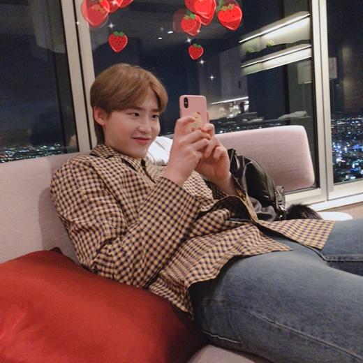 Lee Jong Suk có biểu cảm cực gian khiến fan tò mò anh chàng đang làm trò gì trên điện thoại.