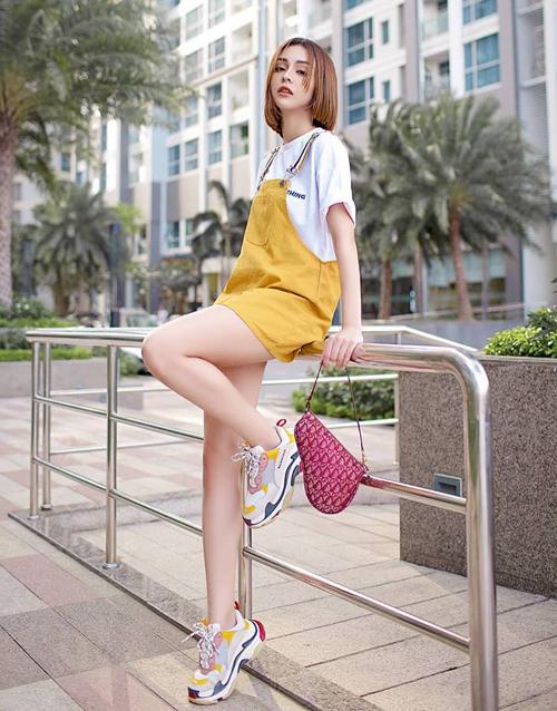 Set đồ yếm của MLee vốn đã màu sắc càng thêm phần rực rỡ khi cô nàng diện cùng sneakers Balenciaga và túi Dior tông xuyệt tông.