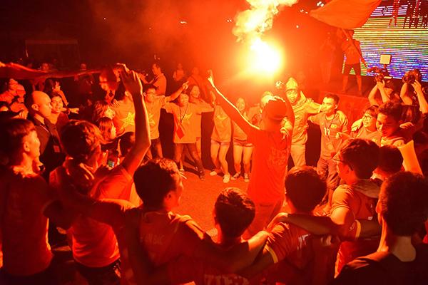 Tại sân thể thao của ĐHY Hà Nội,các cổ động viên là sinh viên khoác áo cờ đỏ sao vàng, khoác tay nhau reo hò. Pháo sáng đã được đốt lên để ăn mừng.