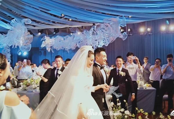 Trương Hinh Dư diện váy cưới lộng lẫy, nắm tay chồng bước vào lễ đường. Cặp đôi nở nụ cười hạnh phúc ngọt ngào trên môi.