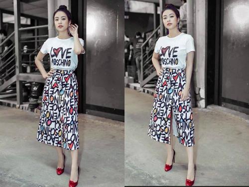 Áo phông mix cùng chân váy xẻ đùi của Moschino năng động, cá tính nhưng cũng không kém phần tự tin, nổi bật trên ghế nóng. Bông tai tua rua và giày cao gót đính nơ là bộ đôi phụ kiện điểm xuyết hoàn hảo cho set đồ.