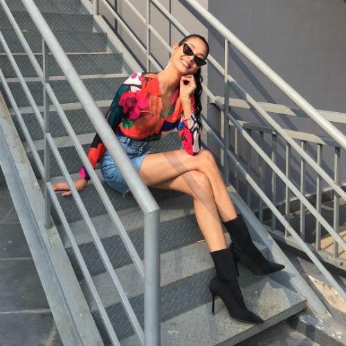 Đa phần boots trong tủ đồ của Hoàng Thùy có màu đen. Boots cao cổ phối hợp cùng quần short jeans và áo hoa tạo nên vẻ ngoài bụi phủi, năng động cho Á hậu 9X.