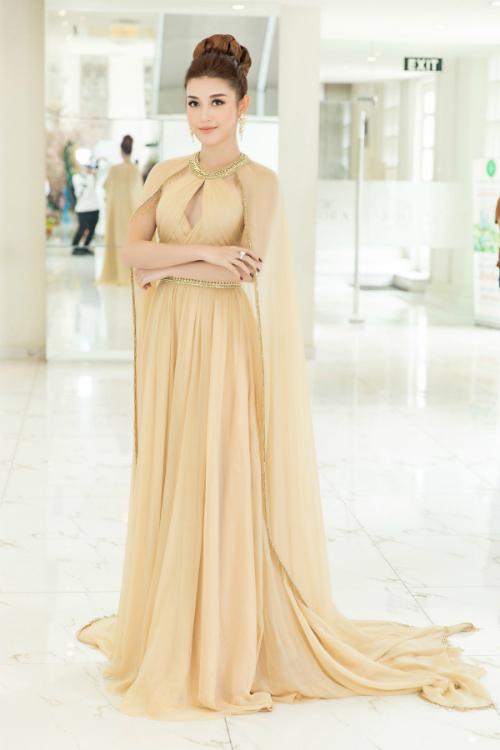Lựa chọn đầm dáng cape chất liệu mềm mại, gam màu vàng đồng của NTK Lê Thanh Hòa, Huyền My tựa như một nàng công chúa. Kiểu tóc búi cao và lối trang điểm nhẹ nhàng tôn lên vẻ đẹp tự nhiên của Á hậu Việt Nam 2014.