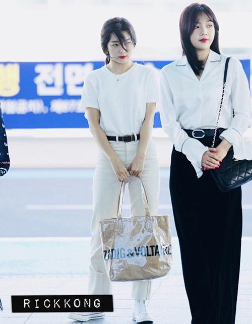 Hai thành viên Red Velvet đều mặc áo trắng nhưng có phong cách khác nhau. Seul Gi kết hợp áo phông, quần jean sáng màu, túi to bản tiện dụng. Joy lại mix sơ mi với quần ống rộng, chuẩn style công sở.