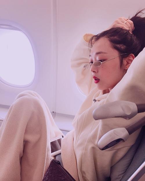 Sulli đeo kính nhỏ xíu hợp mốt, thoải mái ngồi co chân trên máy bay.