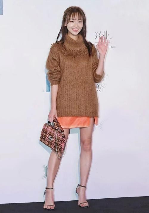 Trong một sự kiện của Vogue, Ngô Cẩn Ngôn gây chú ý với chiếc  áo len cao cổ dày dặn, rộng thùng thình che phủ chân váy ngắn.