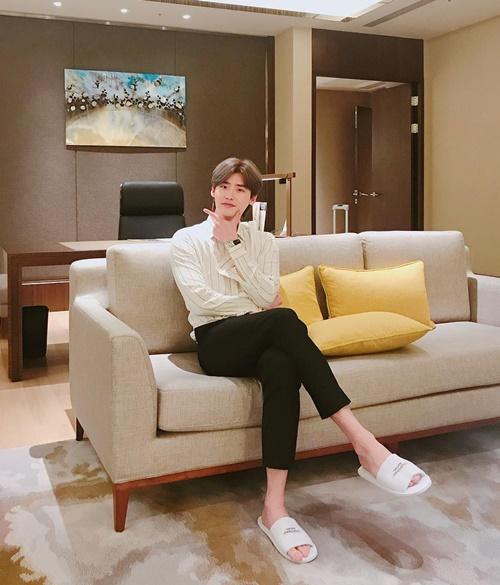 Lee Jong Suk thích kiểu đầu bổ luống, ngồi vắt chân tạo dáng.