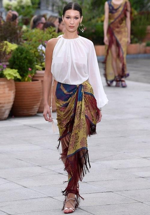 Em gái Gigi, Bella Hadid cũng catwalk tại show của Oscar de la Renta. Cô thả rông vòng 1 trong set đồ lấy cảm hứng từ váy quấn sarong Ấn Độ.