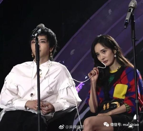 Dương Mịch ngồi cạnh Hoa Thần Vũ xem biểu diễn, cầm một sợi dây trên áo nam ca sĩ xoay vòng vòng trên tay.
