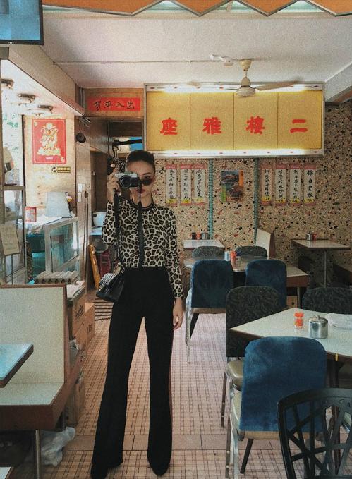 Dạo chơi Hồng Kông, Yến Trang diện áo sơ mi họa tiết da báo để kết hợp cùng quần suông cạp cao. Bộ trang phục giúp Én chị ăn gian chiều cao hiệu quả.