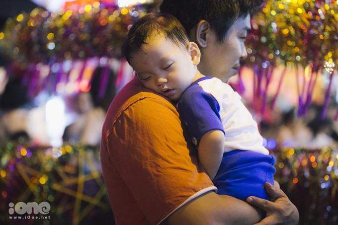 <p> Một em nhỏ ngủ gục trên vai bố.</p>