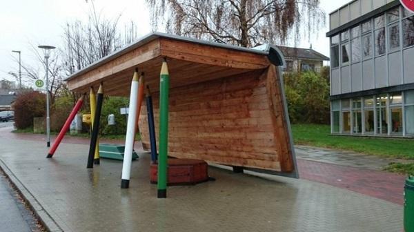 Trạm xe buýt của trường học này được thiết kế giống như một quyển sách được chống đỡ bằng những cây bút chì. Ý tưởng thiết kế thật phù hợp để đặt trong khuôn viên các trường học dành cho trẻ em.