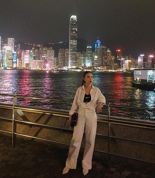 Yến Trang diện cây trắng dạophố phường Hong Kong về đêm rực rỡ ánh đèn.