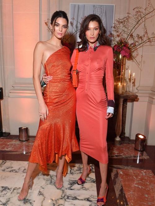 Cả hai chân dài chứng minh sự ăn ý trong style dự tiệc: cùng diện đầm đỏ, cùng cầm theo ly rượu vang sành điệu trên tay. Bella chọn kiểu tóc gợn sóng nhẹ còn Kendall buộc tóc đuôi ngựa.