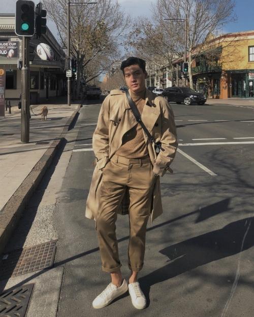 Trench coat dáng dài được Quang Đại phối cùng áo cổ 3 phân và quần âu tone sur tone gam màu be. Túi xách và sneakers làm điểm nhấn hoàn hảo cho trang phục.