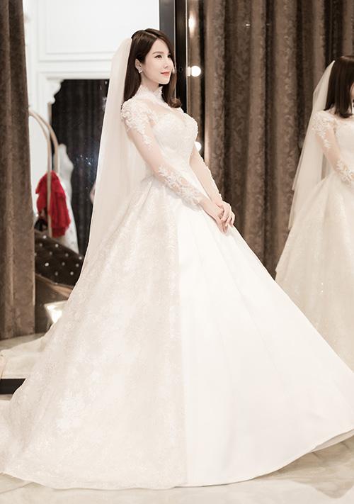 Chiếc váy cưới Diệp Lâm Anh mặc trong hôn lễ là sản phẩm của NTK Phạm Đăng Anh Thư. Bộ trang phục lấy cảm hứng cổ điển với phần cổ cao, tay dài xuyên thấu đáp ren kết hợp cùng cúp ngực. Thiết kế tôn lên hiệu quả thân hình gợi cảm của Diệu Lâm Anh.
